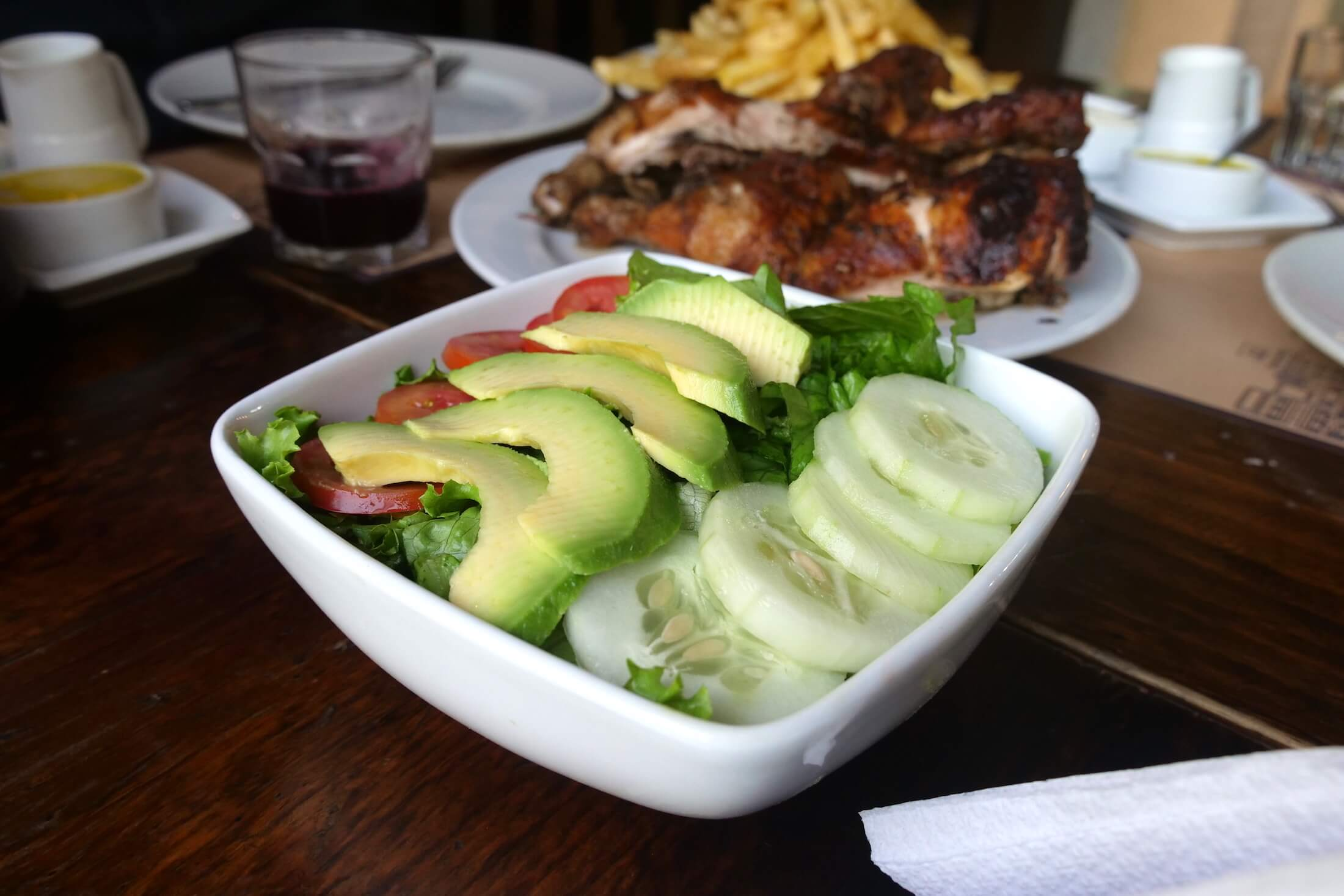 simple and clean plate of crunchy vegetables and avocado to accompany your Pollo a la Brasa